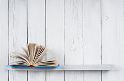 The open book on a wooden shelf. Royalty Free Stock Images