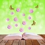 Open book on a wooden surface  with  flowers  and butterflies Stock Images