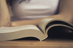 Open book on wooden table closeup. Back blurred the background you can see a girl reading a book. Vintage processing Stock Photography