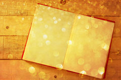 Open book on wooden table with glitter gold lights Stock Photo