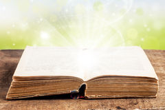 Open book on a wooden table with light effects Royalty Free Stock Image