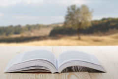 Open book on wooden table on natural blurred background.  Stock Photo