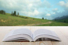 Open book on wooden table on natural blurred background. Back to school. Copy Space.  Royalty Free Stock Photography