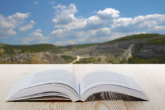 Open book on wooden table on natural blurred background. Back to school. Copy Space.  Stock Photography