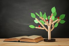 Open book and wooden tree puzzle over blackboard background. education and knowledge concept. Open book and wooden tree puzzle over blackboard background royalty free stock photos
