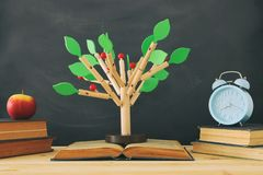 Open book and wooden tree puzzle over blackboard background. education and knowledge concept. Open book and wooden tree puzzle over blackboard background stock photo
