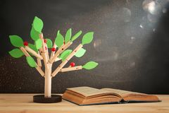 Open book and wooden tree puzzle over blackboard background. education and knowledge concept. Open book and wooden tree puzzle over blackboard background royalty free stock images