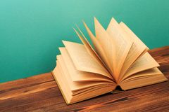 Open book on wooden vintage table blue background. Image royalty free stock photo