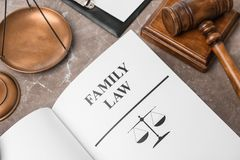 Open book with words FAMILY LAW, scales of justice. And gavel on table, closeup stock images