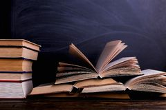 Open books are a stack on the desk, against the background of a chalk board. Difficult homework at school, a mountain of knowledge. Open books are mountain on stock images