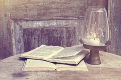 Open books on the old wooden table near the lamp Royalty Free Stock Photos