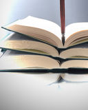Open books and pen. Three open books with pen, studio shot Royalty Free Stock Image
