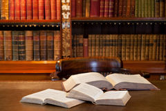 Open books in study or library. Open books on wooden table with old volumes of books on shelves in background; library or study scene Stock Photo