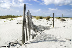 Open Border. A delapitated fence falls and casts a long shadow on the dunes Stock Image