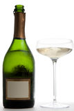 Open Bottle of Champagne Next to a Glass. An opened green bottle of champagne (with a blank label) next to a saucer style champagne glass.  Studio isolated on a Stock Photo