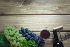 Open bottle of red wine with a glass, corkscrew and ripe grape on a wooden background. Copy space. Royalty Free Stock Photography
