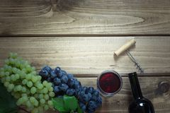 Open bottle of red wine with a glass, corkscrew and ripe grape on a wooden background. Copy space. Stock Photos