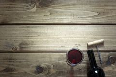 Open bottle of red wine with a glass, corkscrew on a wooden background. Copy space. Open bottle of red wine with a glass, corkscrew on a wooden background. Copy Stock Images