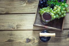 Open bottle of red wine with wineglass, corkscrew and ripe grape on wooden board. Copy space and top view. Open bottle of red wine with wineglass, corkscrew and royalty free stock photo