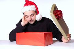 Open the box. Man with santa hat looks in a present box Royalty Free Stock Photo