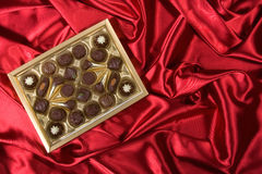 Open box with chocolates. Golden chocolates box on red satin background Royalty Free Stock Image