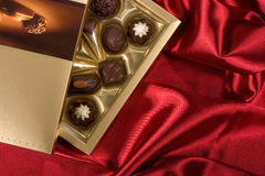 Open box with chocolates. Golden chocolates box on red satin background Royalty Free Stock Images