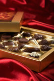 Open box with chocolates. Golden chocolates box on red satin background Stock Images