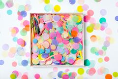 Open box with confetti. Open box with bright confetti on colorful background royalty free stock photo