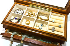 Open Box With Jewelry. An open jewelry box with bracelets, necklaces, rings, earrings and a watch stock images