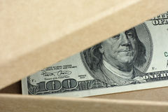 Open box with one hundred dollars banknote in it. Conceptual image Royalty Free Stock Images