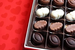 Open box of Valentine's chocolates. Open box of Valentine's day chocolates with milk,dark and white filled chocolates inside,arranged on red heart paper Stock Photos
