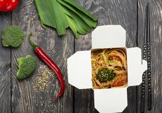 Open box-wok with noodles, near pepper and broccoli, on wooden surface. Open box-wok with noodles, near pepper and broccoli, on grey wooden surface Stock Images