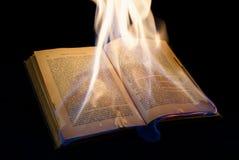 Open brennendes Buch mit schwarzem Hintergrund Stockfotografie