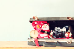 Open briefcase with christmas decorations and camera in front of beach view. christmas holiday concept Stock Image