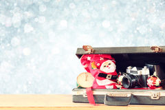 Open briefcase with old camera and christmas decoration over bokeh blurred background Royalty Free Stock Image