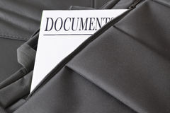 Open briefcase with some documents in it. A paper with the title DOCUMENTS written on it. Stock Images