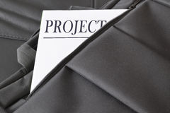 Open briefcase with some documents in it. A paper with the title PROJECT written on it. Royalty Free Stock Photos