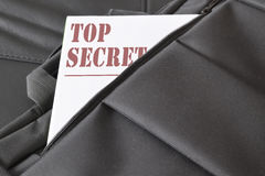 Open briefcase with some documents in it. A paper with the title TOP SECRET written on it. Stock Photo