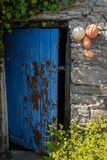 An open broken painted door held open with a piece of string of a traditional stone building in Ireland. Nobody in the image stock image