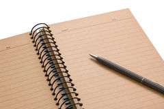 Open brown note book with lined and gray pen on white background Stock Photos