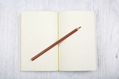 Open brown notebook and a pencil on white wooden table, top view Stock Image