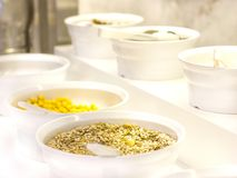 Open buffet in the hotel. Variety of corn flakes, muesli and granola on white bowls stock photos