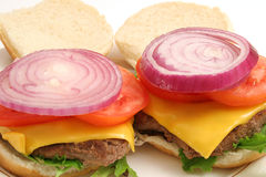 Open burgers w/onion on top. Shot of open burgers w/onion Royalty Free Stock Photography