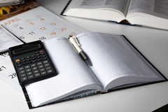 Open business diary with pen and calculator Stock Photo