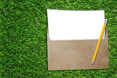 Open Business Envelope. Blank white paper and yellow pencil on green grass background, nature and ecology concept Royalty Free Stock Images