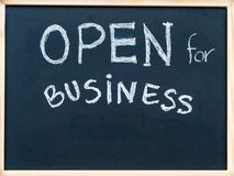 Open for business sign message handwritten with white chalk on on wooden frame blackboard Royalty Free Stock Photo