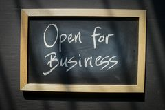 Open for business - words written with chalk on blackboard stock images