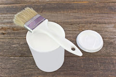 Open can of white enamel paint with brush Stock Image