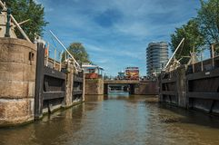 Open canal sluice gate, bridge and building under sunny blue sky in Amsterdam. Amsterdam, northern Netherlands - June 27, 2017. Open canal sluice gate, bridge Royalty Free Stock Image