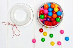 Open candy jar filled with gum balls on white wood. Overhead view of an open glass candy jar filled with colorful gum balls on white wood Royalty Free Stock Image